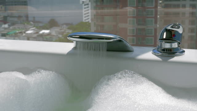Woman running bath with foam video