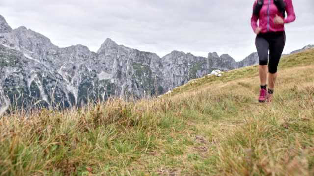 LD Woman running down a grassy path high in the mountains Wide locked down low angle shot of a female runner running down a grassy meadow on a ridge high in the mountains. Shot in Slovenia. pedal pushers stock videos & royalty-free footage