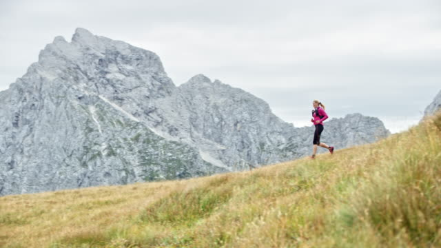 DS Woman running down a grassy ridge overlooking the nearby mountains Wide dolly shot of a female runner descending a grassy mountain ridge with a view of the nearby mountain peaks. Shot in Slovenia. pedal pushers stock videos & royalty-free footage