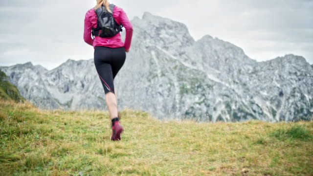 DS Woman running high in the mountains Wide low angle dolly shot of a woman running high in the mountains on a grassy path overlooking the nearby mountain. Shot in Slovenia. pedal pushers stock videos & royalty-free footage