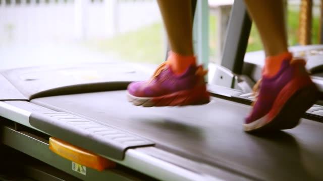 vídeos de stock e filmes b-roll de woman running in a gym on a treadmill concept for exercising, fitness and healthy lifestyle - aparelho de musculação