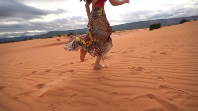 Woman running in sand dunes