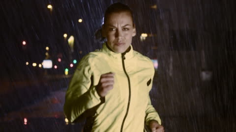 SLO MO TS Woman running in the city on a rainy night Slow motion medium tracking shot of a woman running along a city street at night in heavy rain and is focused on her exercise. determination stock videos & royalty-free footage