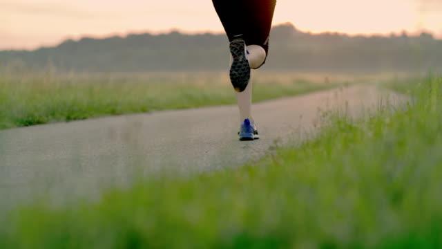 vidéos et rushes de slo mo femme qui court dans le pays à l'aube - joggeuse