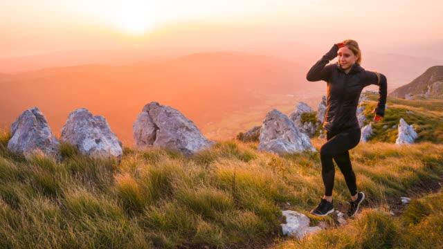 kvinnan kör i bergen vid solnedgången - jogging hill bildbanksvideor och videomaterial från bakom kulisserna