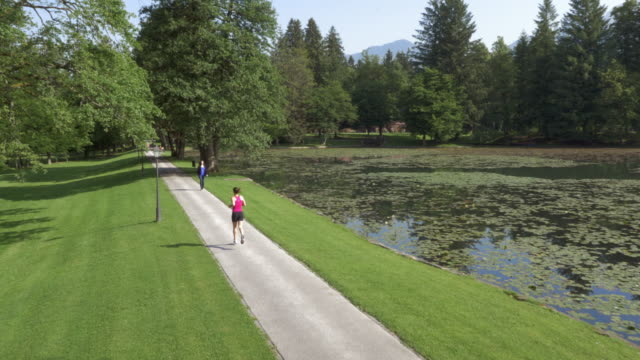 AERIAL Woman running in the park along a lake video