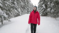 istock woman running in the snowy forest 1199759713