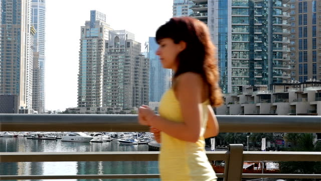 Woman running jogging in Dubai Marina in the morning, slow motion video