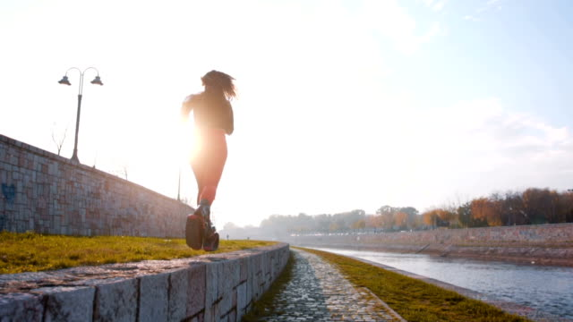 Woman running near river in kangoo jump shoes
