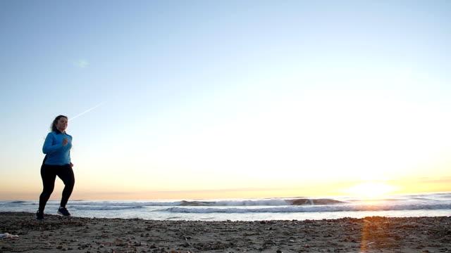 夕暮れ時、海の近く走っている女性 - 女性選手点の映像素材/bロール