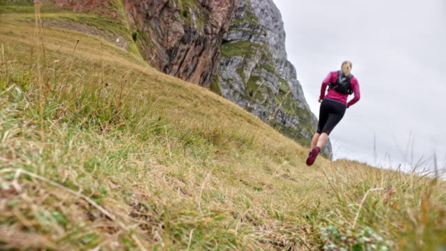 LD Woman running on a meadow high in the mountains Wide locked down low angle shot of a female runner running across a meadow high in the mountains. Shot in Slovenia. pedal pushers stock videos & royalty-free footage