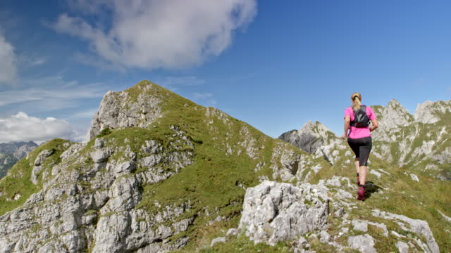 SLO MO Woman running on a mountain ridge on rough terrain on a sunny day Slow motion wide handheld shot following a woman running across a high mountain ridge with a beautiful view on a sunny day. Shot in Slovenia. pedal pushers stock videos & royalty-free footage