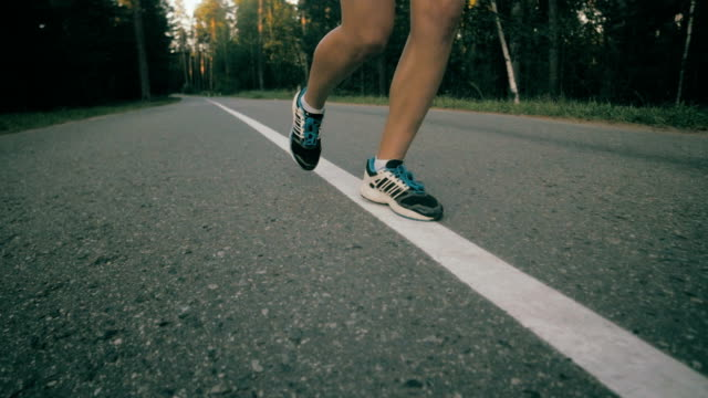 Woman running on asphalt road, super slow motion video