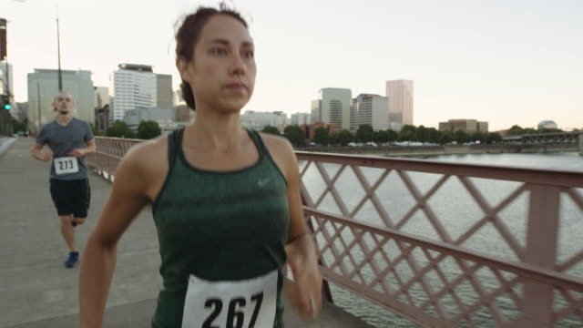 UHD 4K: SLO MO Woman running on bridge with beautiful cityscape in the background video