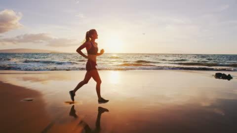 vídeos de stock e filmes b-roll de woman running on the beach - correr