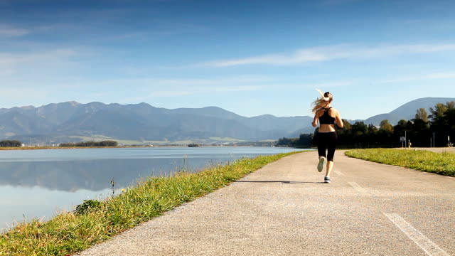 Woman running on the shore of the lake and mountains video