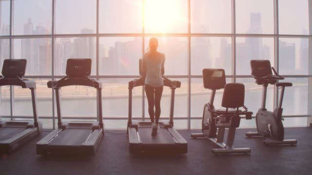 Woman running on treadmill at a panoramic window with city view at the sunrise.