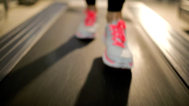 Woman running on treadmill, close up on shoes video