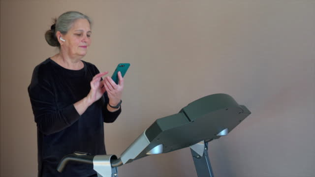 woman running on treadmill during morning work out. chatting on her smartphone - runner rehab gym video stock e b–roll