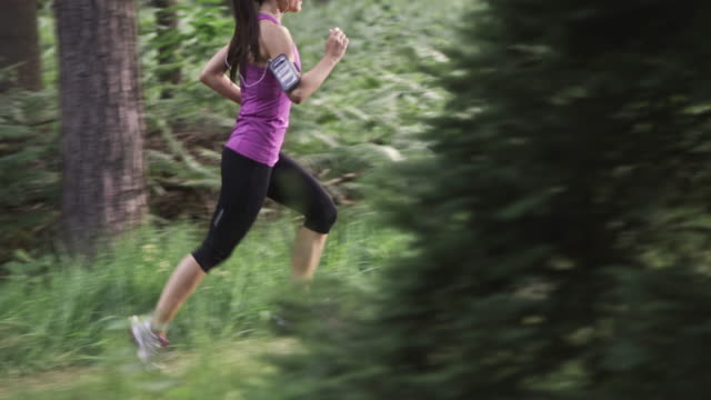 SLO MO DS TU Woman running through the forest video