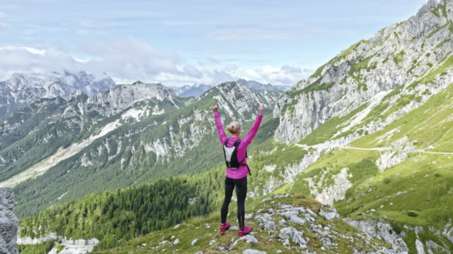 AERIAL Woman running to the mountain ridge and raising her hands in the air above the sunny valley Aerial shot of a female runner running to the end of a ridge high in the mountains and raising her hands in the air above the sunny valley below the mountain. Shot in Slovenia. top garment stock videos & royalty-free footage
