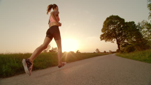SLO MO TS Woman running towards setting sun Slow motion medium low angle tracking shot of a brunette woman with a pony tail running on a road in nature and towards the setting sun. recreational pursuit stock videos & royalty-free footage