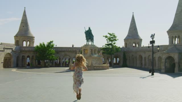 Woman running towards St. Stephen statue