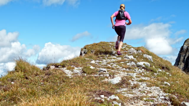 SLO MO Woman running up a mountain ridge in sunshine Slow motion wide low angle handheld shot of a woman running up a mountain ridge on a sunny day. Shot in Slovenia. pedal pushers stock videos & royalty-free footage