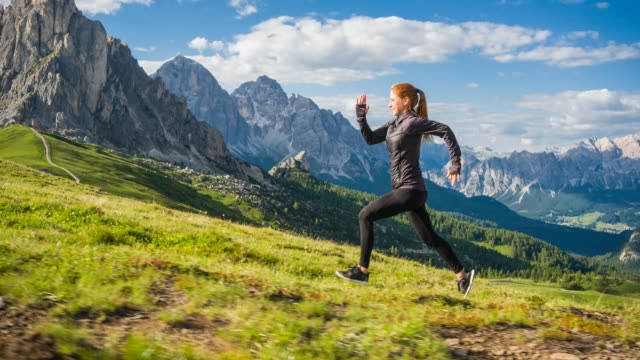 Woman running uphill on a grassy meadow with mountains in background