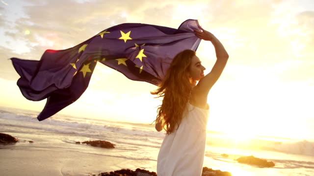 Woman running with european flag on beach video