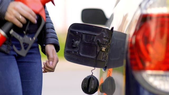 bir kadın bir benzin istasyonunda benzin araba çalışır. yakın çekim. - i̇stasyon stok videoları ve detay görüntü çekimi