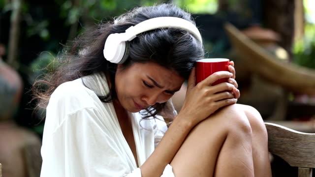 vídeos de stock e filmes b-roll de woman sad unhappy girl in big headphones listening music  broken heart love concept - criança perdida