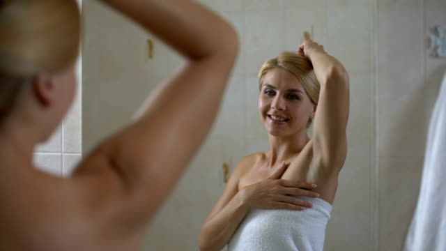 Woman satisfied with soft skin of armpit, high quality antiperspirant, body care video
