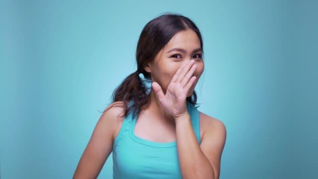 Woman saying secret on isolated blue background 4k