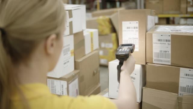 掃描包倉庫中的女人 - postal worker 個影片檔及 b 捲影像