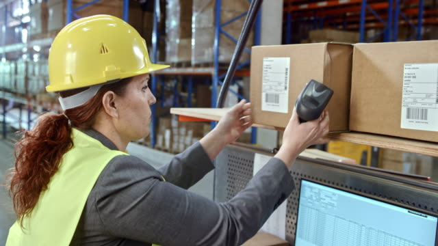Woman scanning the packages on her desk in warehouse with a handheld scanner video
