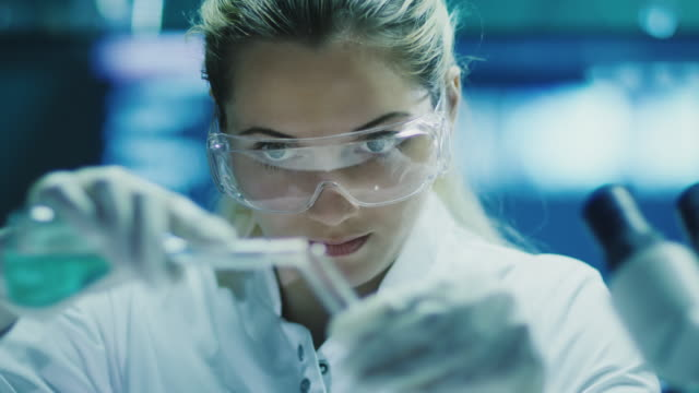 woman scientist in glasses does chemical research - chemistry stock videos and b-roll footage