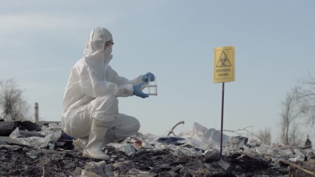woman scientist in uniform and protective gloves holding test tubes taking sample of garbage from the big dirty dump near a sign biological hazard