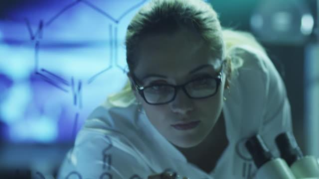 Kadın bilim adamı çizim organik kimyasal formüller üzerinde cam var. 4 k (UHD) kırmızı sinema makinesinde vurdu. video