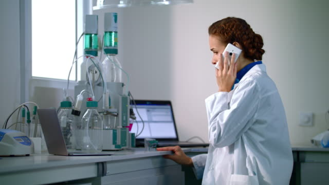 Woman scientist talking on phone in laboratory. Scientist in lab video