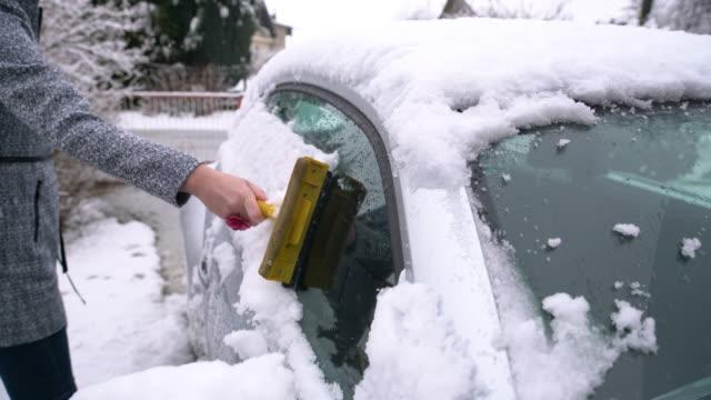 kvinna skrapa snö av bil - vindruta bildbanksvideor och videomaterial från bakom kulisserna