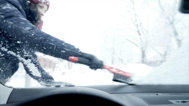 vidéos et rushes de femme de racler la neige sur le pare-brise de la voiture. - raclette