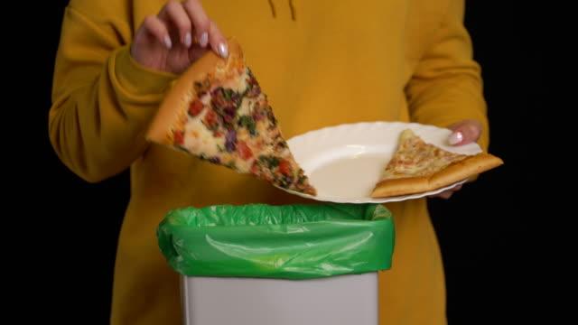 woman scraping with a plate a pizza into garbage bin. - węglowodan jedzenie filmów i materiałów b-roll