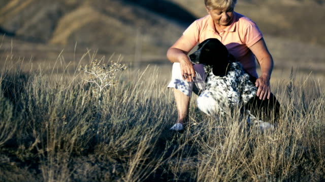 woman scratches a dog in the grass video