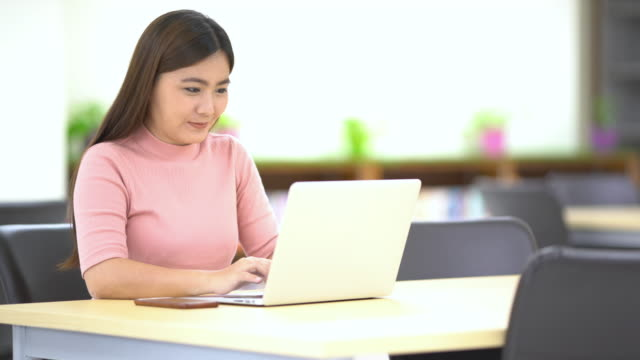 Woman searching a laptop in the library video