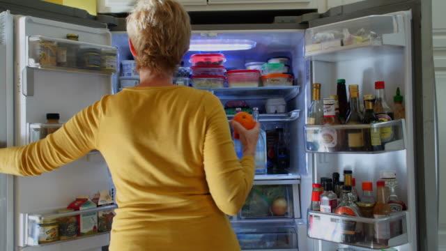 kvinna söker refridgerator för ett mellanmål - fett näringsämne bildbanksvideor och videomaterial från bakom kulisserna