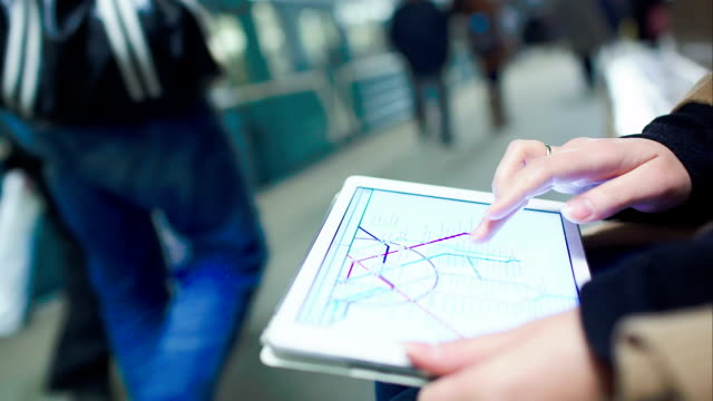 Woman searching station on underground map using touch pad video