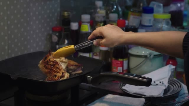 A Woman Searing Chicken In A Frying Pan An Asian Woman Standing At The Stove And Searing Chicken In A Frying Pan in Kitchen seared stock videos & royalty-free footage