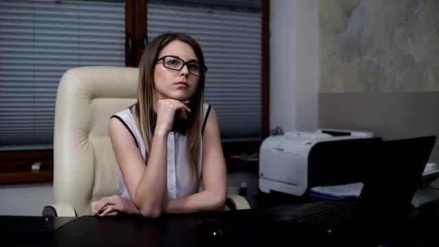vidéos et rushes de rêve de femme secrétaire d'un milieu de travail dans un bureau. fille de la pensée, assis à la table - se reposer