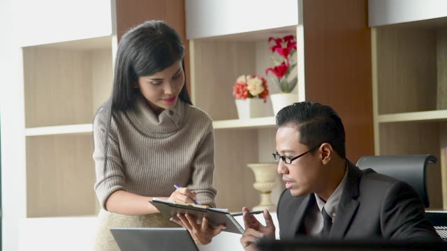 Woman secretary present summary report to executive boss in company office. Asian confident woman intern employee working with businessman present business information. Business Footage concept.